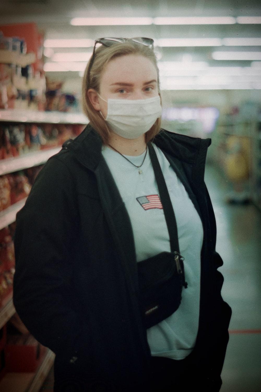 woman in black jacket wearing white face mask