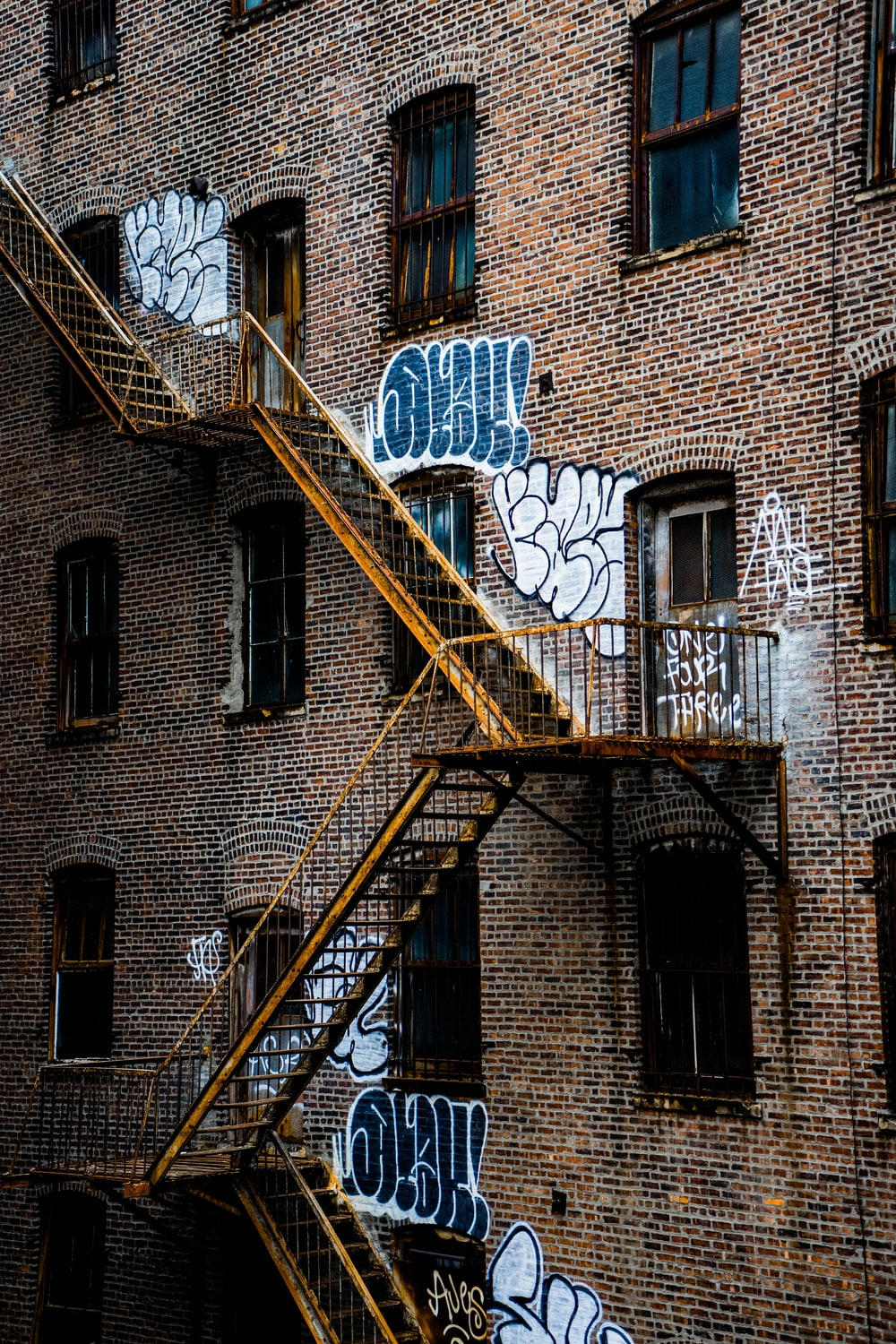 brown brick building with yellow metal ladder