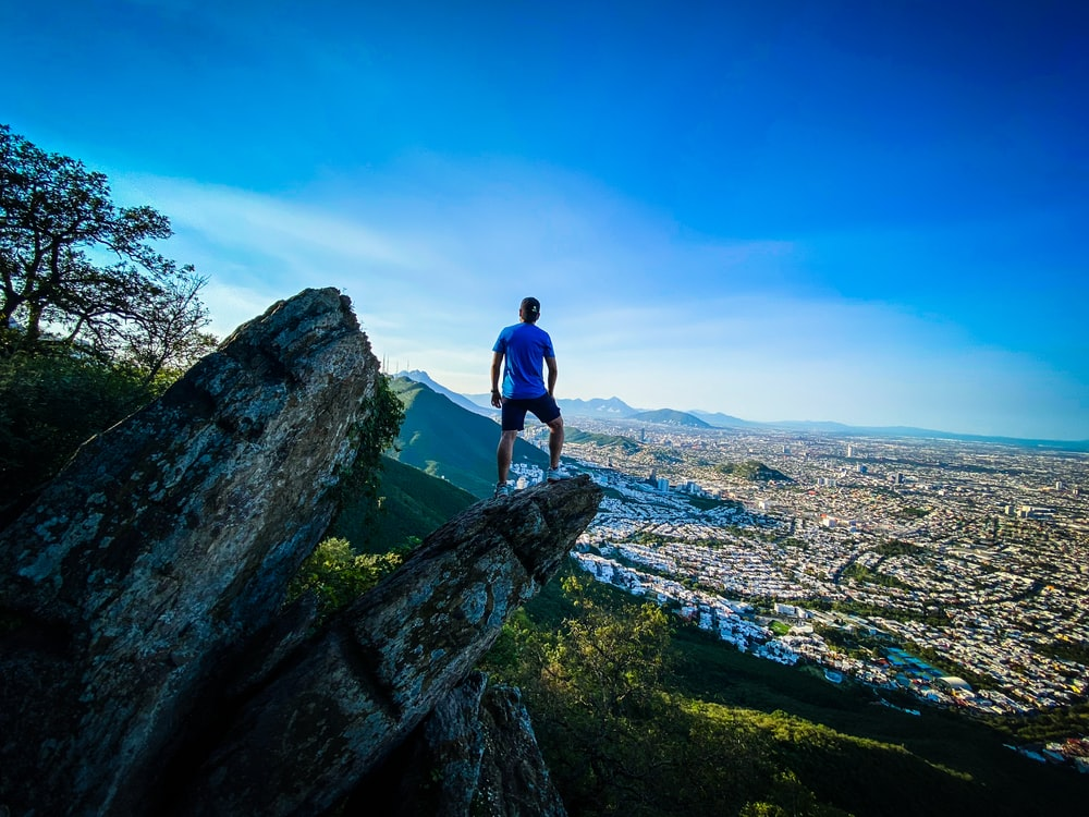 man in blue t-shirt standing on rock during daytime