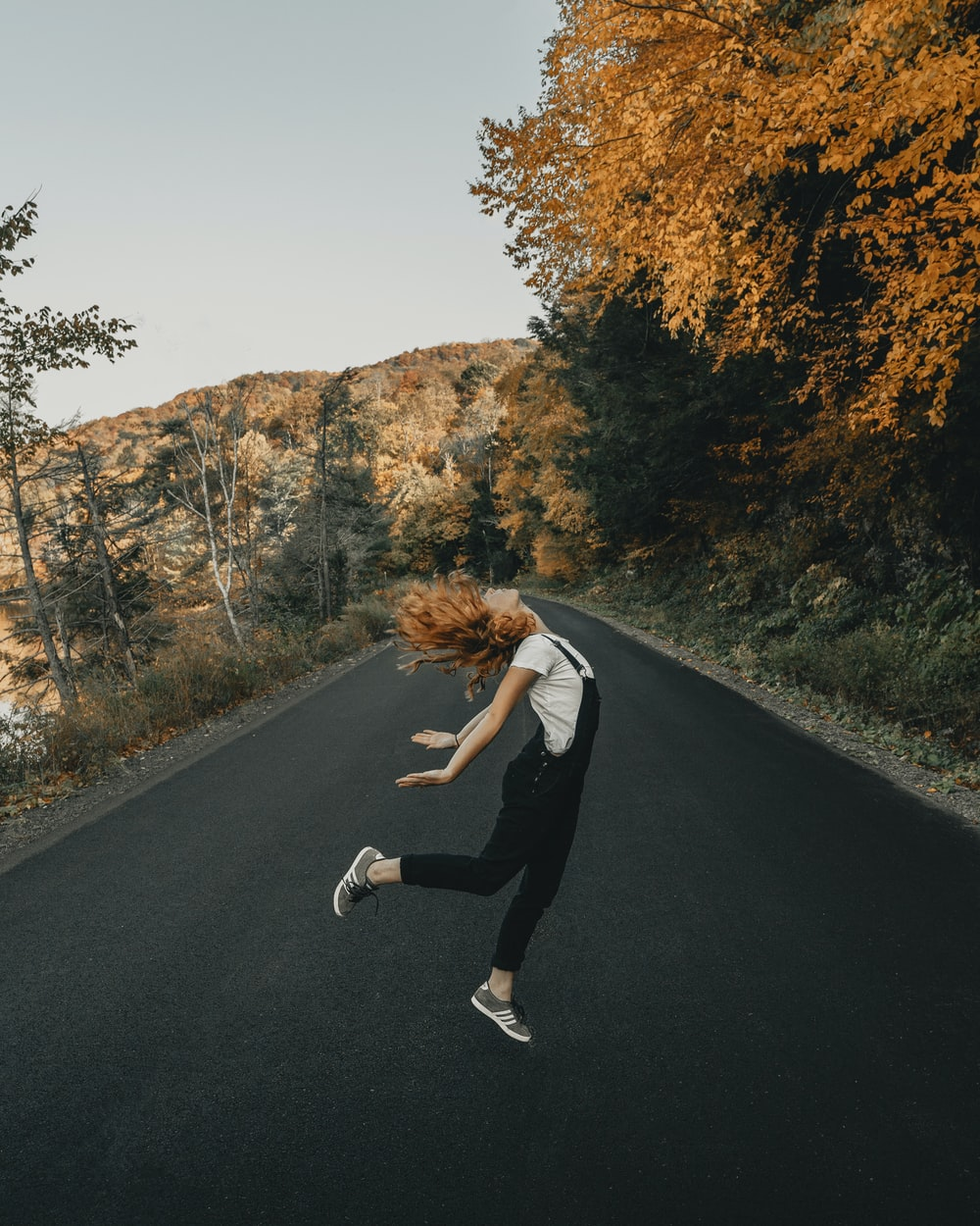 woman in white long sleeve shirt and black pants running on road during daytime