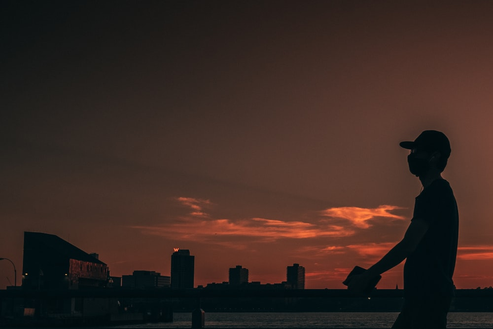 silhouette of man sitting on the edge of a building during sunset