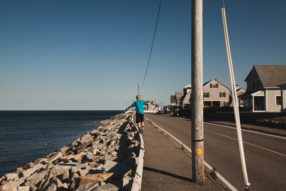 person in green shirt walking on sidewalk near body of water during daytime