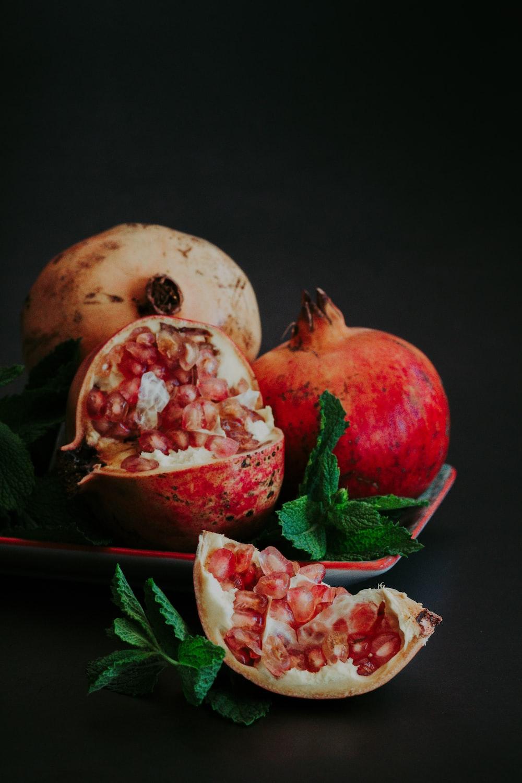 sliced pomegranate fruit on black surface