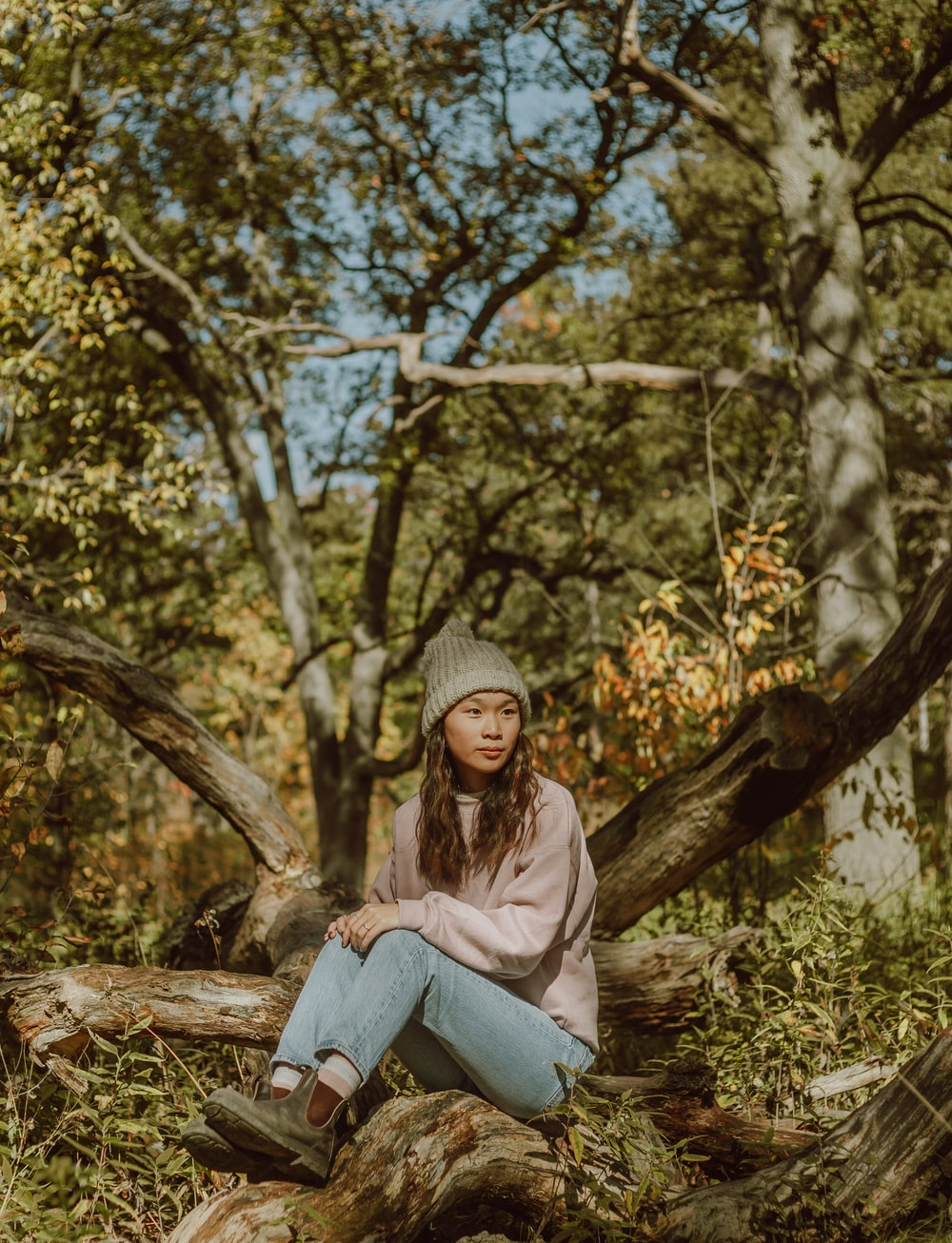 woman in gray knit cap sitting on tree log