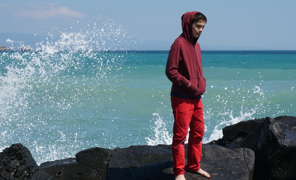 man in red hoodie standing on rock near sea during daytime