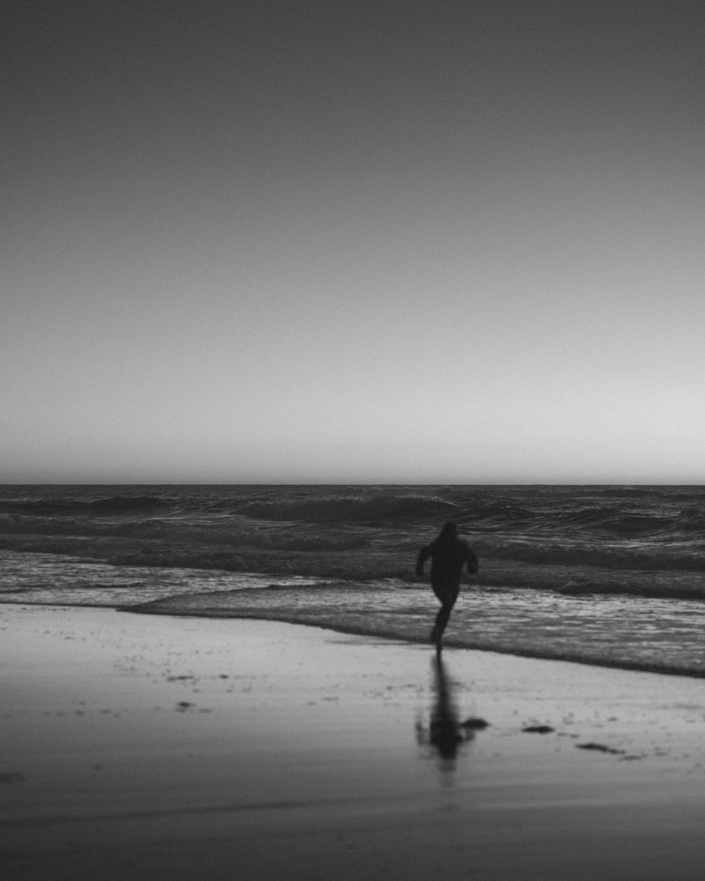 silhouette of person walking on beach during daytime
