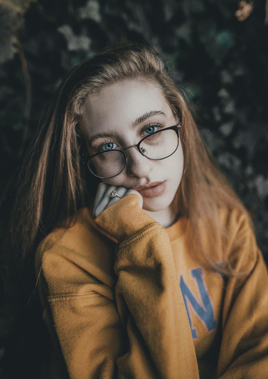 woman in brown hoodie wearing black framed eyeglasses