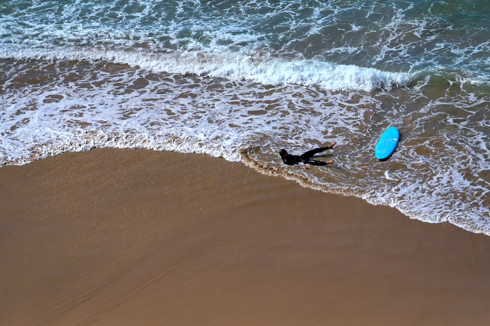 person in black wet suit holding red surfboard on beach during daytime