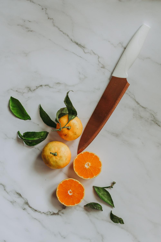 sliced orange fruit beside brown handled knife