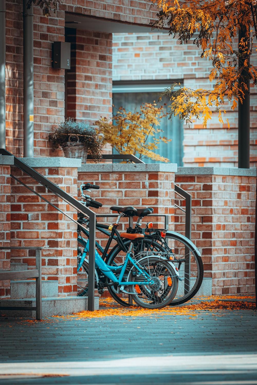 blue city bike parked beside brown brick wall