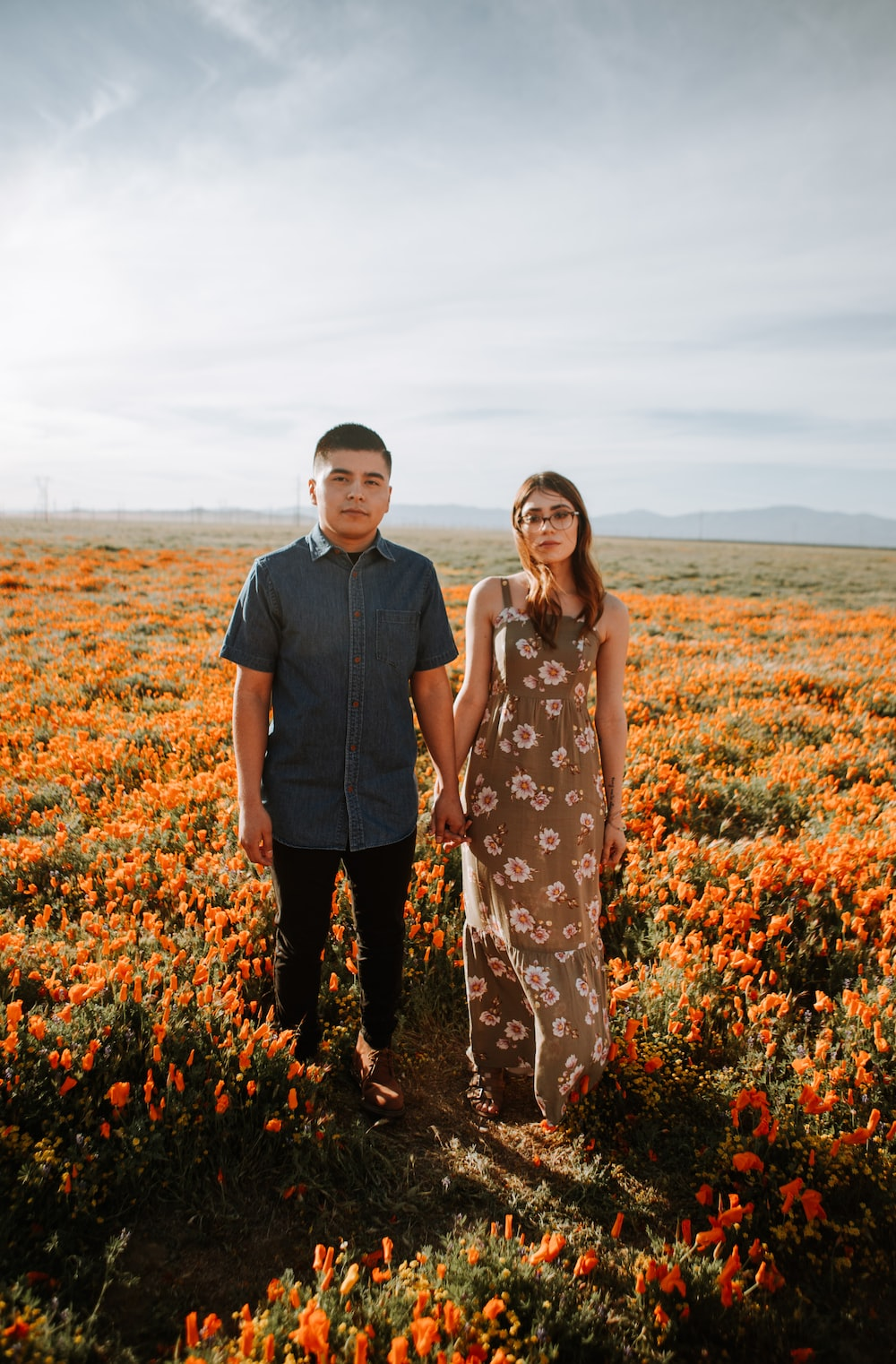man and woman standing on flower field during daytime