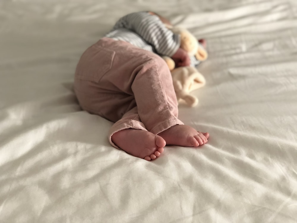 baby in gray and white striped long sleeve shirt and pink pants lying on white bed
