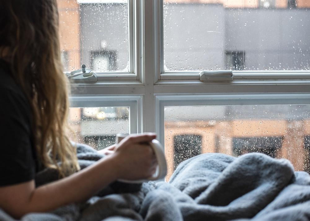 woman in gray sweater sitting beside window