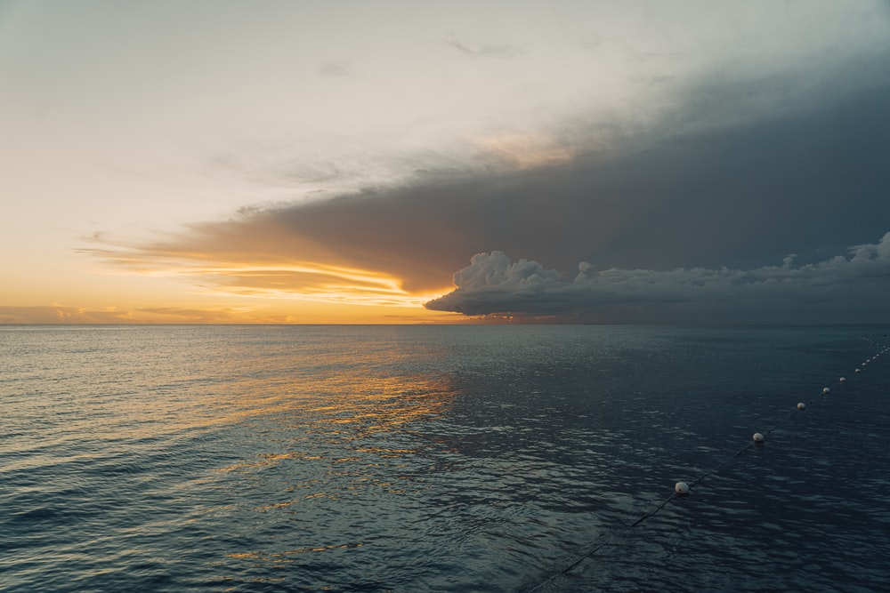 sea under white clouds during sunset