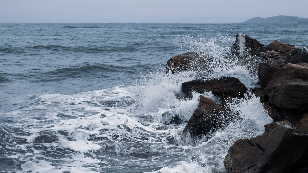 ocean waves crashing on brown rock formation during daytime