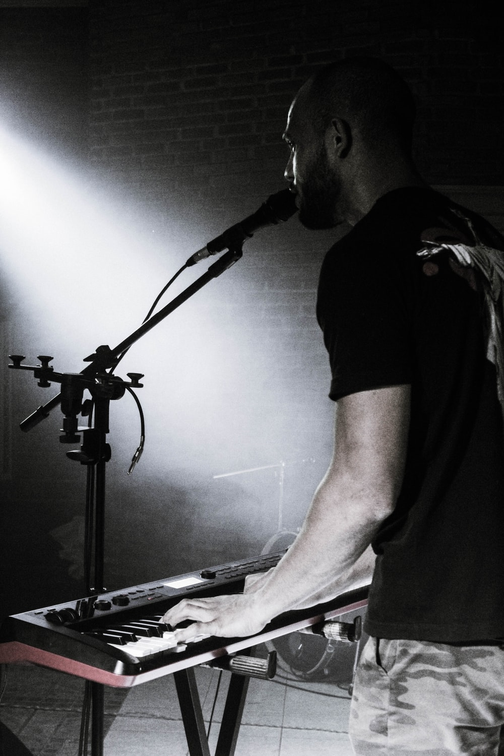 man in black crew neck t-shirt playing electric piano
