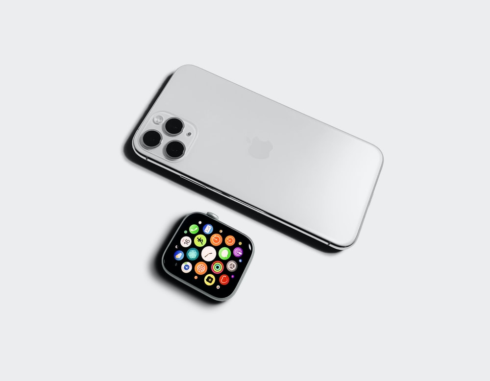 silver iphone 6 beside black and yellow iphone case