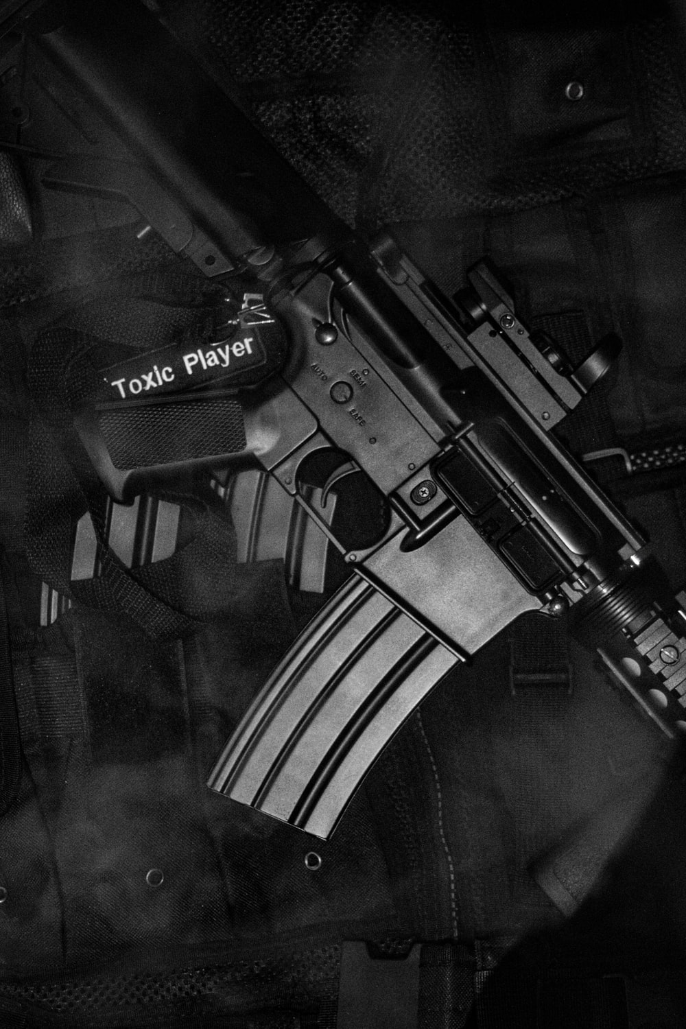 black and white rifle on black textile