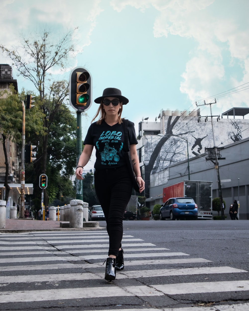 man in green t-shirt and black pants wearing black hat standing on road during daytime