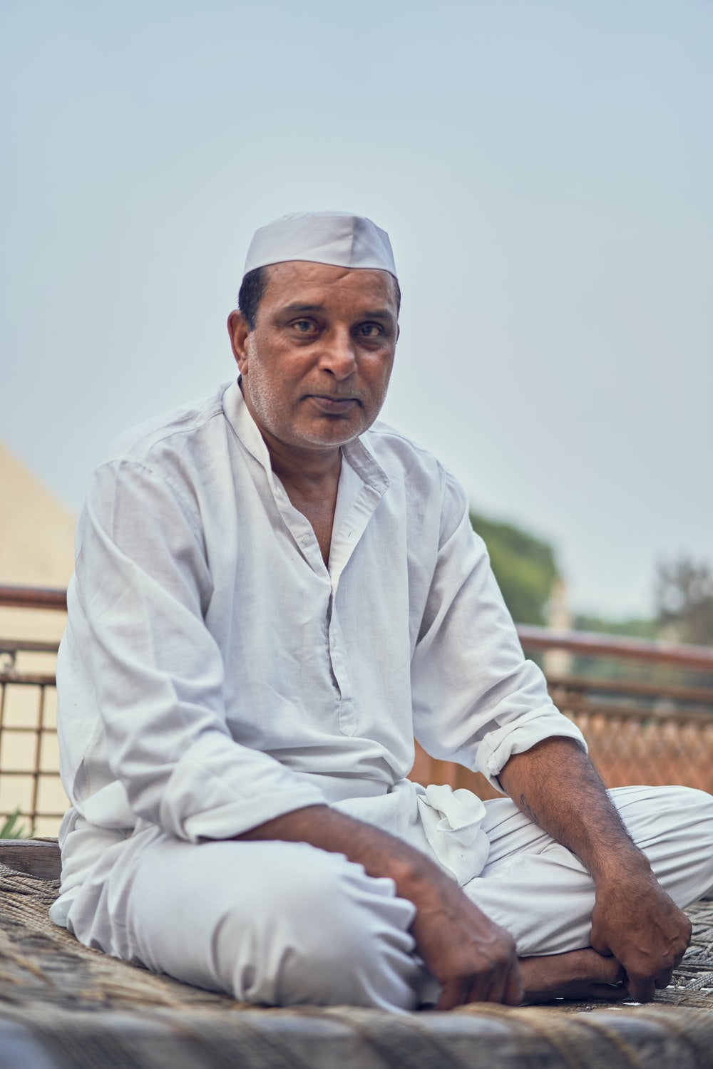 man in white thobe sitting on brown wooden bench during daytime