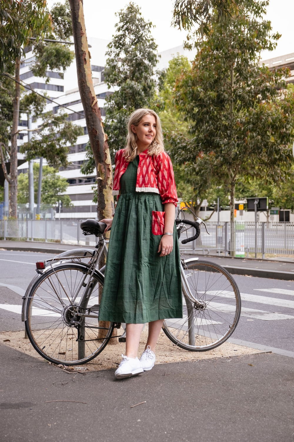 woman in red and green dress standing on road bike during daytime