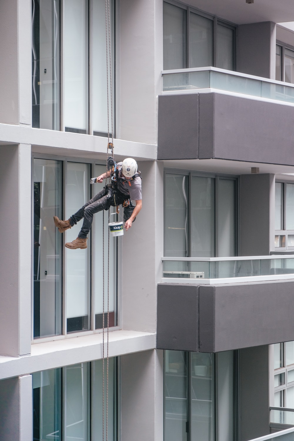 man in black jacket and black pants jumping on window during daytime