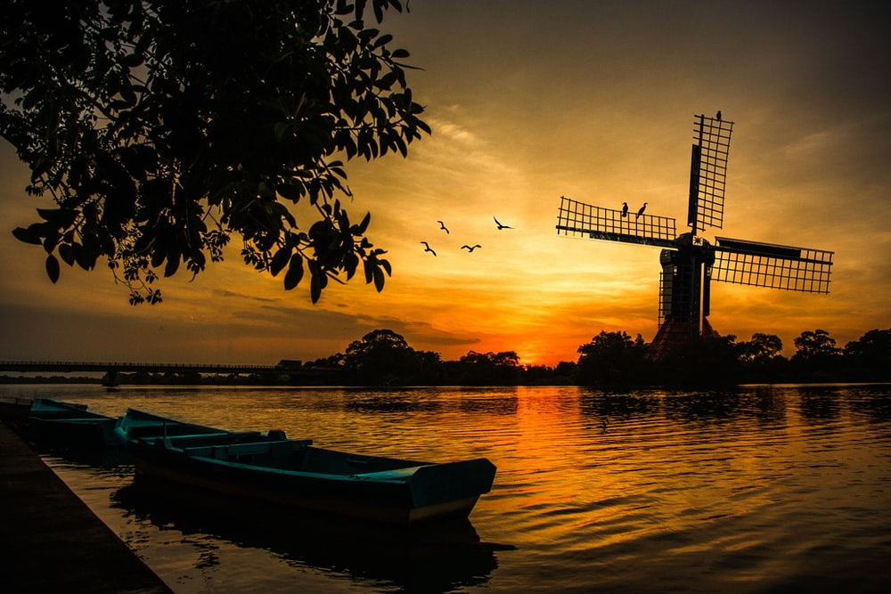 silhouette of boat on water during sunset