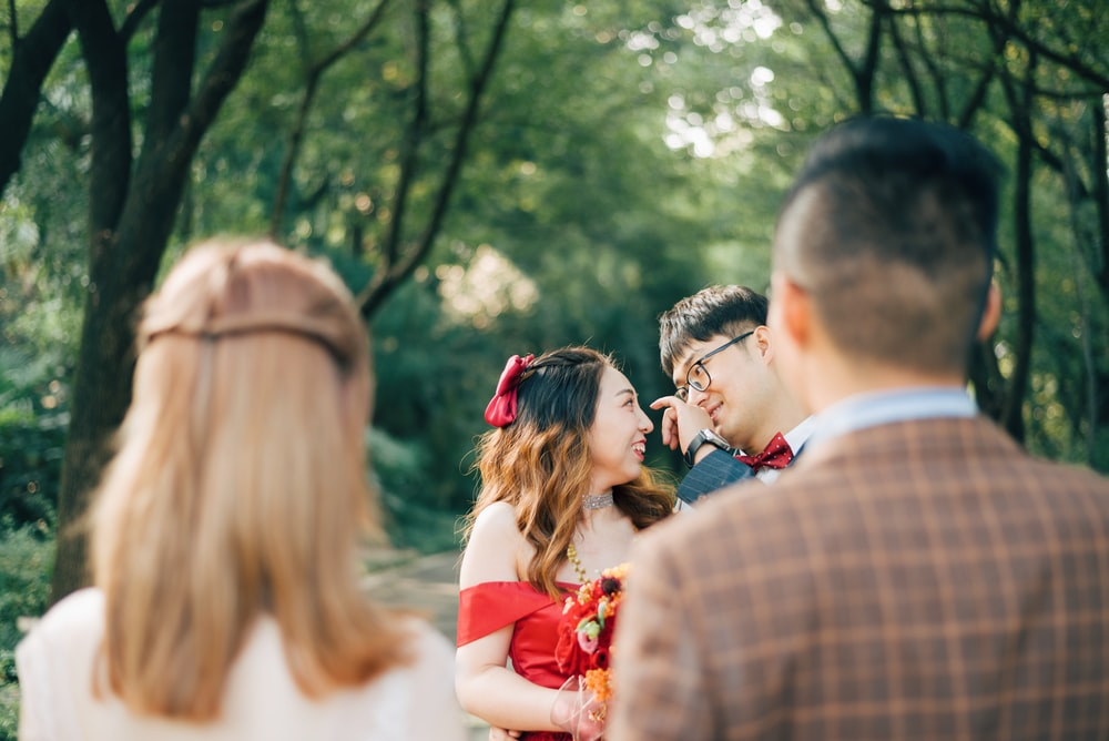 man in brown and white plaid dress shirt standing in front of woman in red dress
