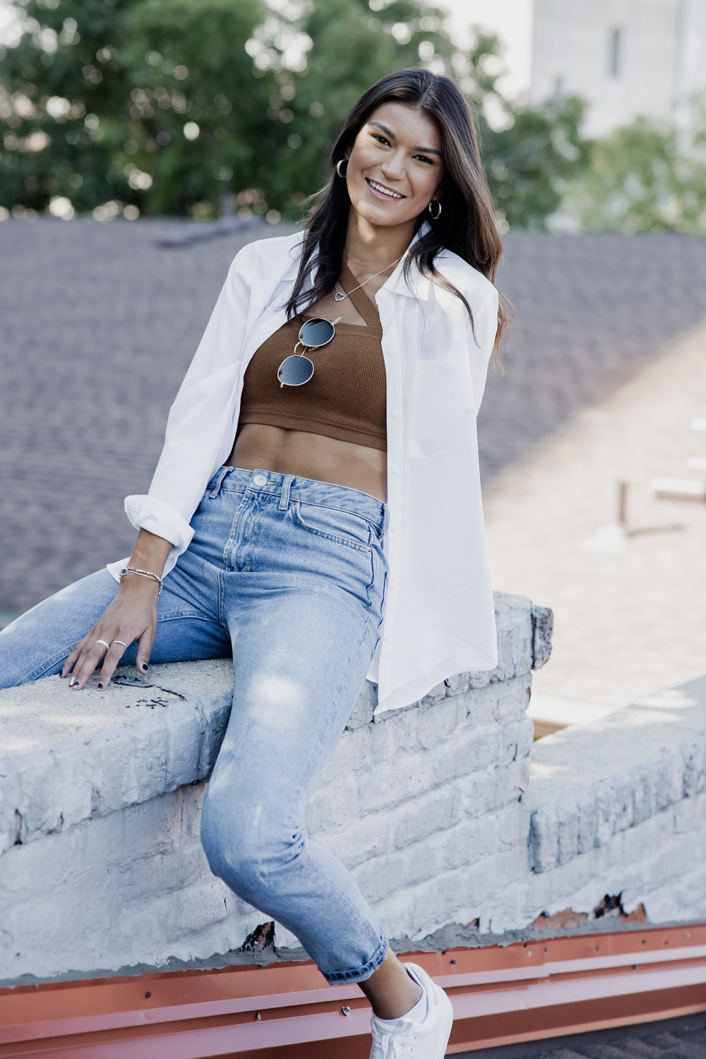 woman in white long sleeve shirt and blue denim jeans sitting on gray concrete bench during