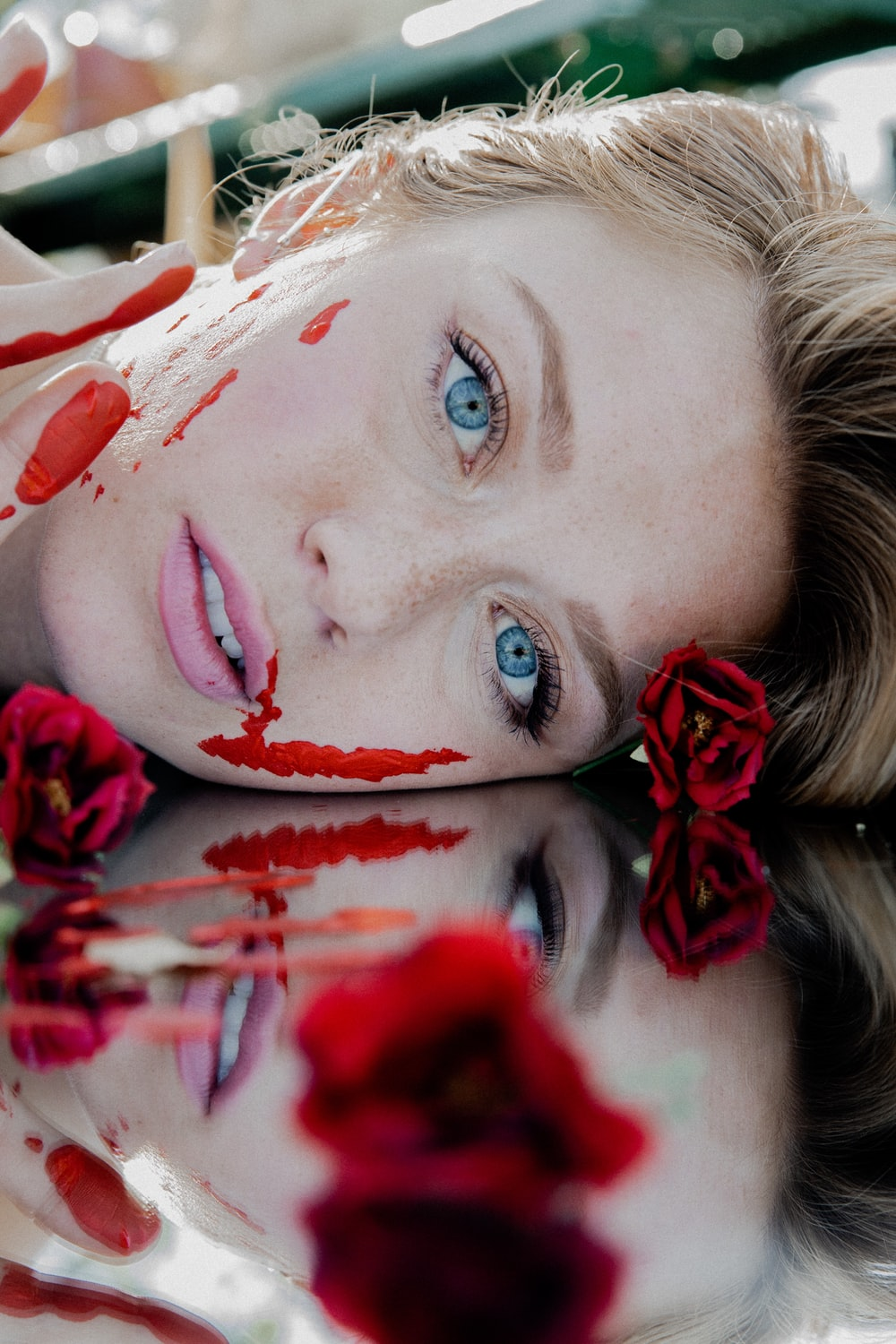 woman with red and white flower petals on her face