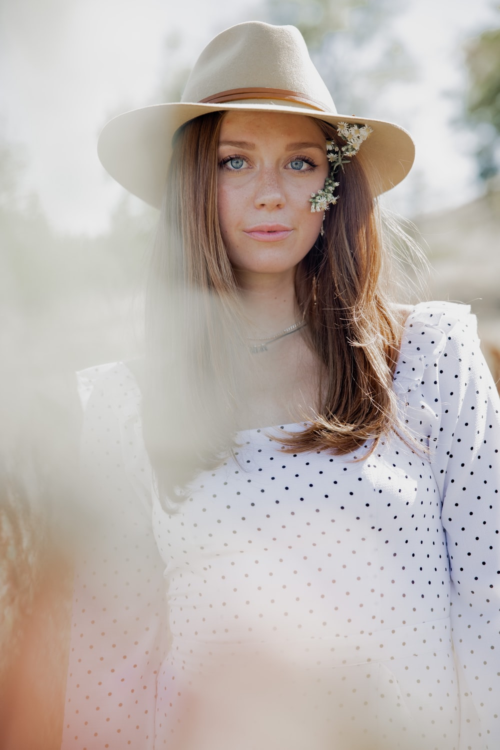 woman in white and red polka dot long sleeve shirt wearing brown hat