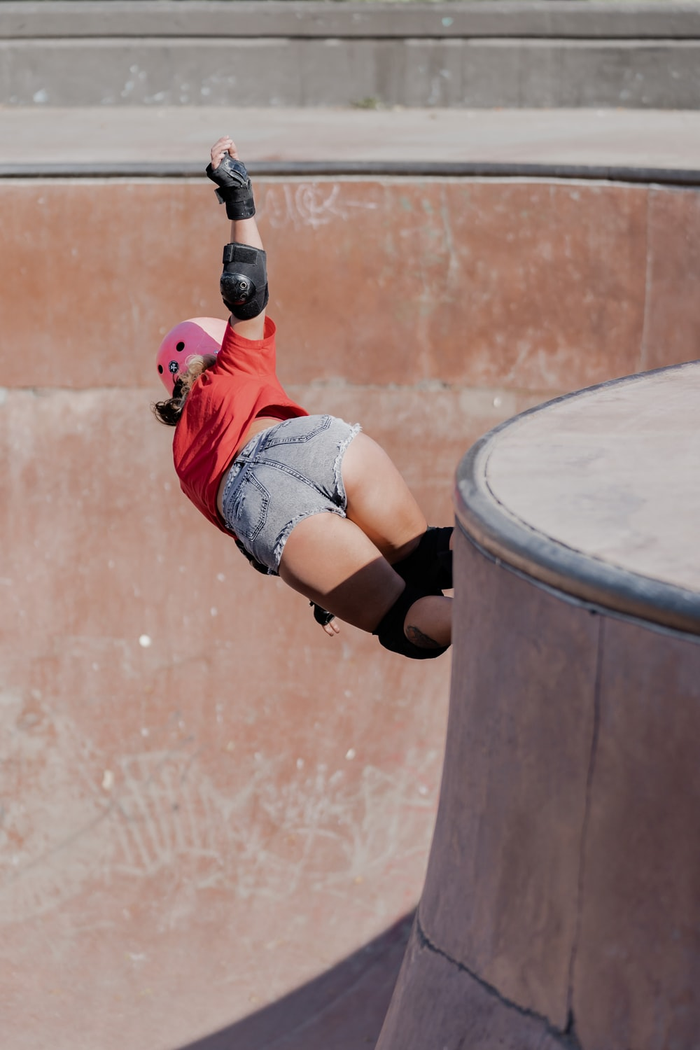 woman in red shirt and blue denim shorts doing skateboard stunts