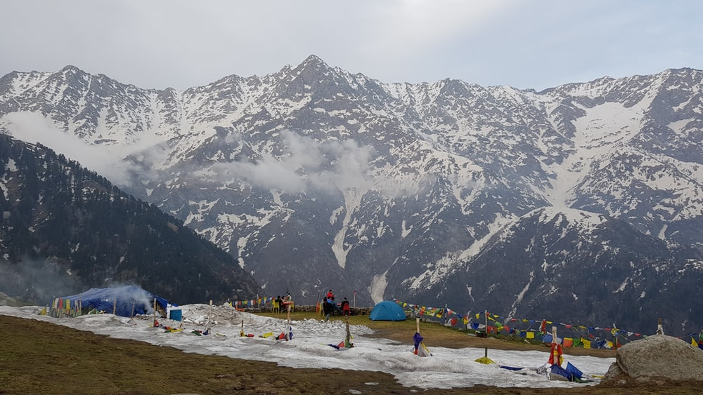 people on beach near snow covered mountain during daytime