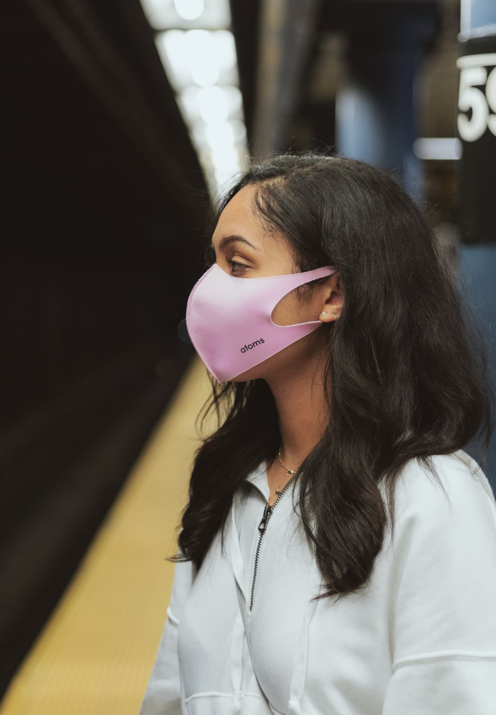 woman in white collared shirt wearing pink mask