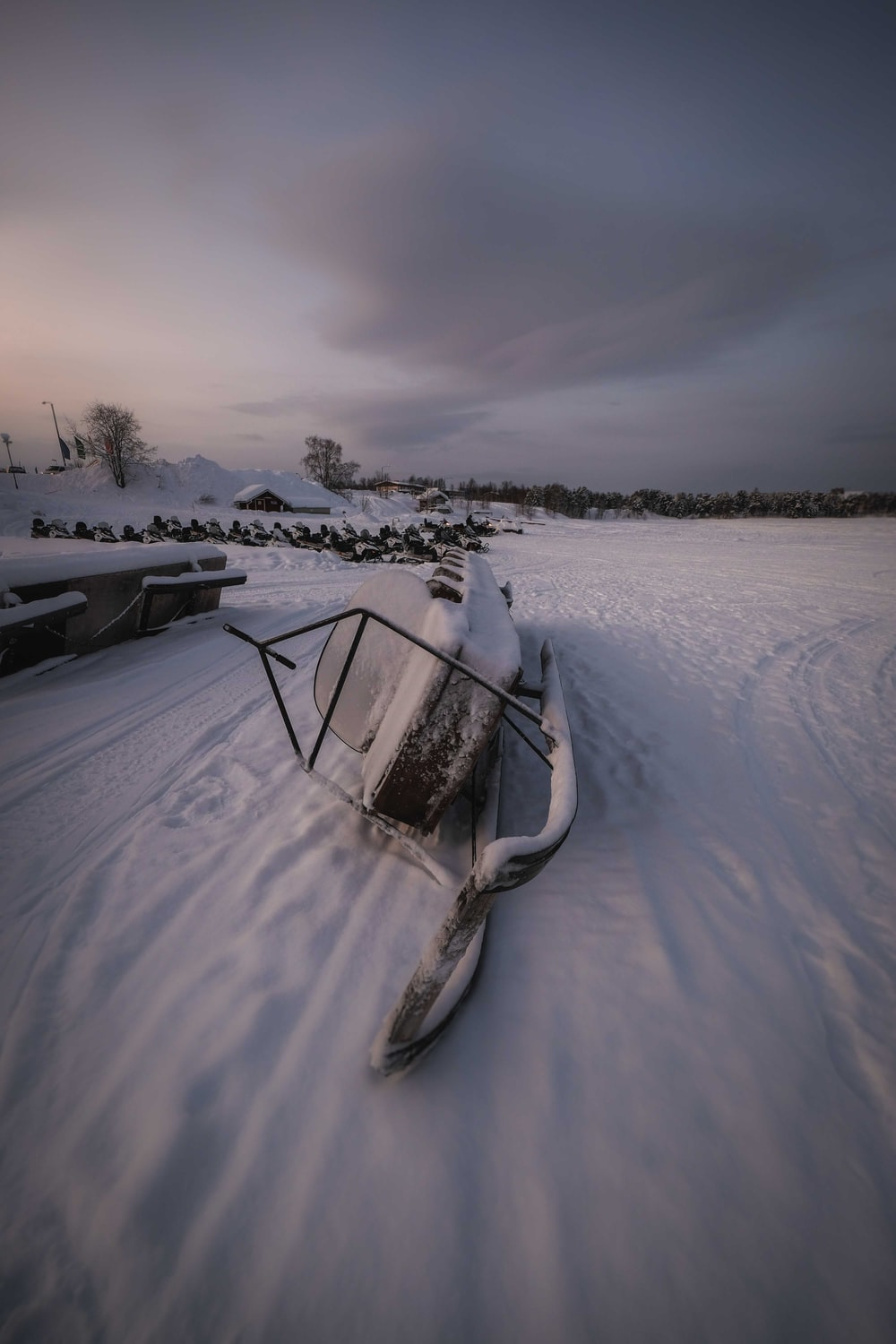 black boat on snow covered ground during daytime