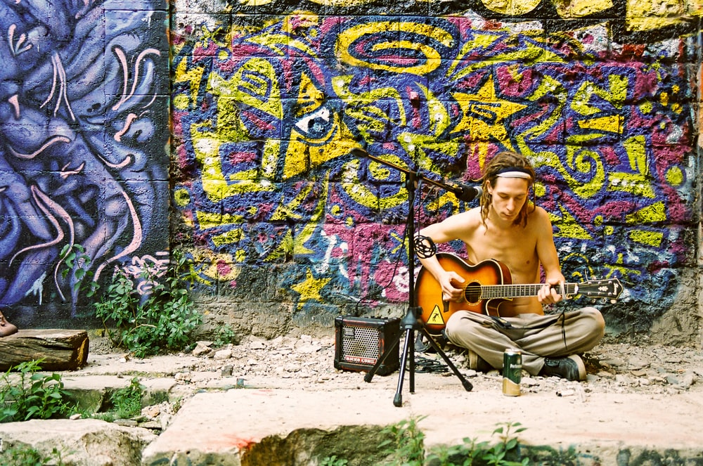 topless man sitting on chair near graffiti wall during daytime