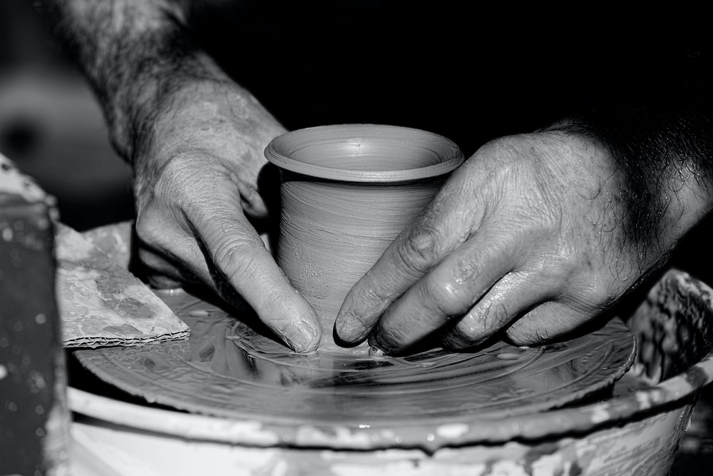 grayscale photo of person holding round plate