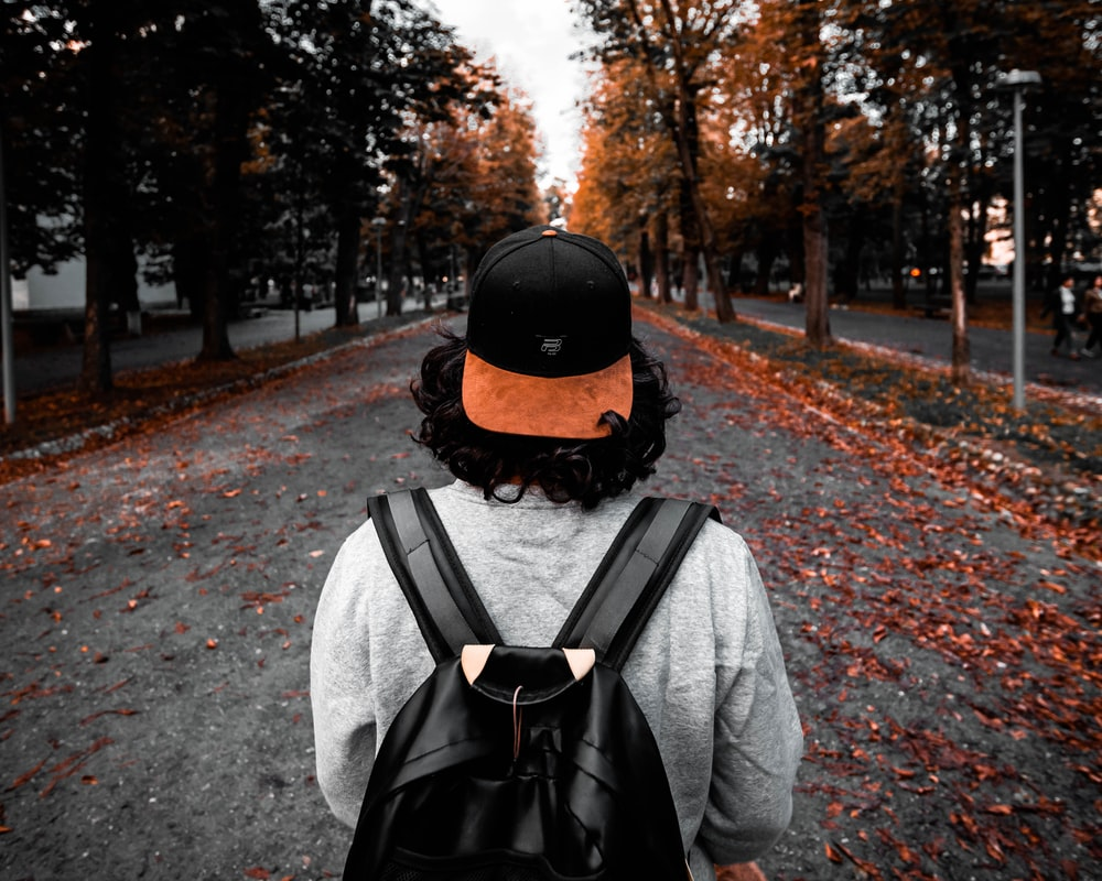 man in gray jacket wearing black backpack walking on road during daytime