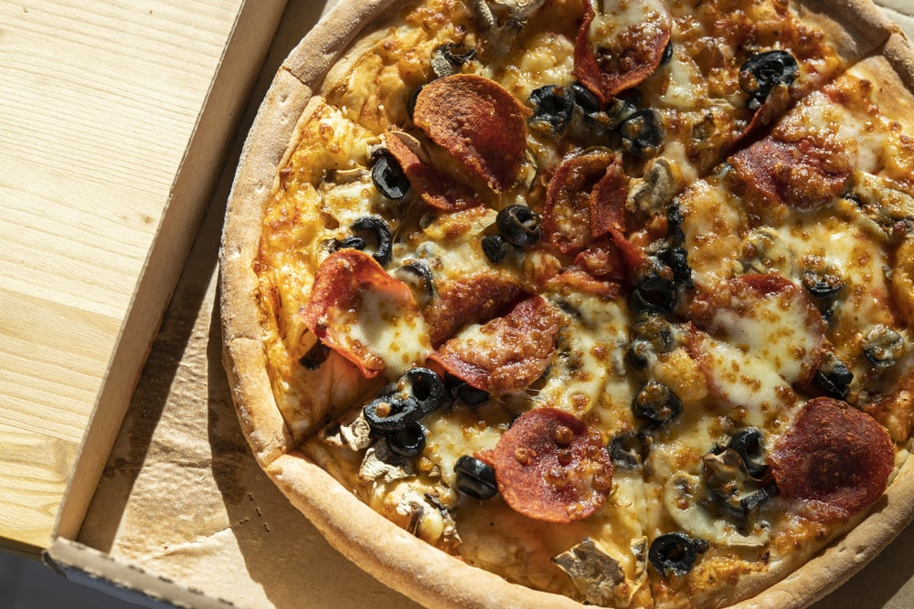 pizza with pepperoni and cheese on brown wooden table