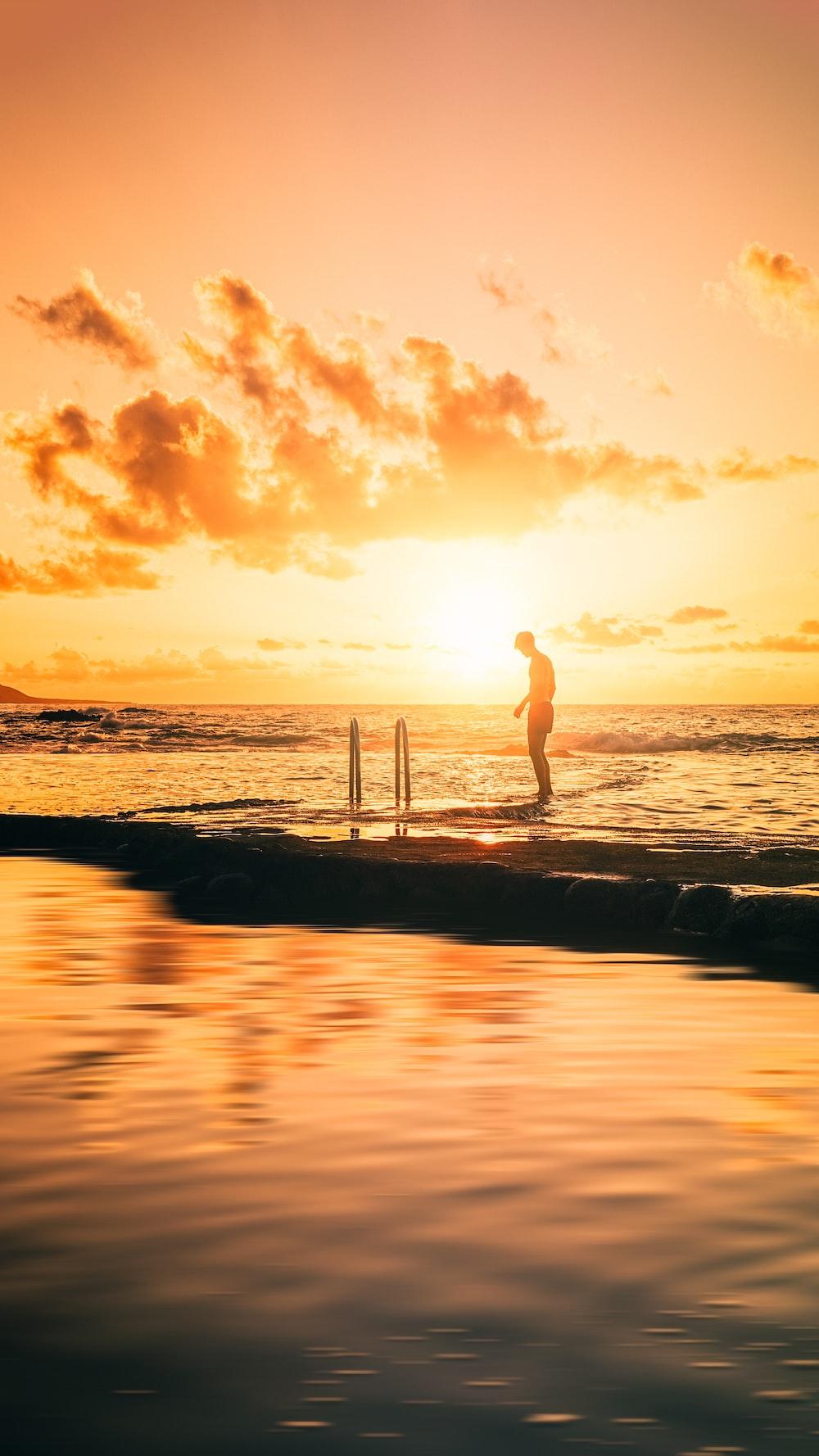 mujer, en, vestido blanco, posición, en, playa, durante, ocaso