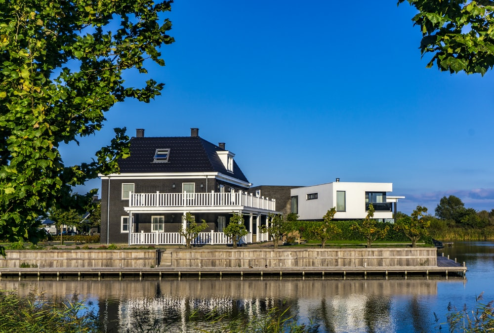 white and black house beside body of water during daytime