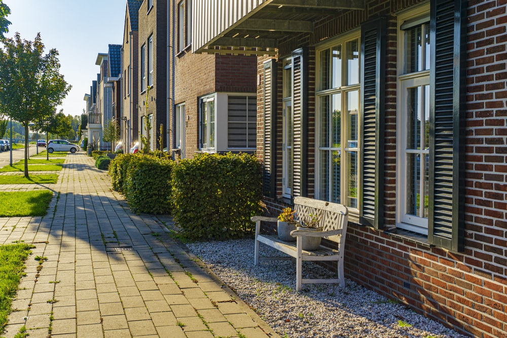 brown wooden bench near brown brick building during daytime