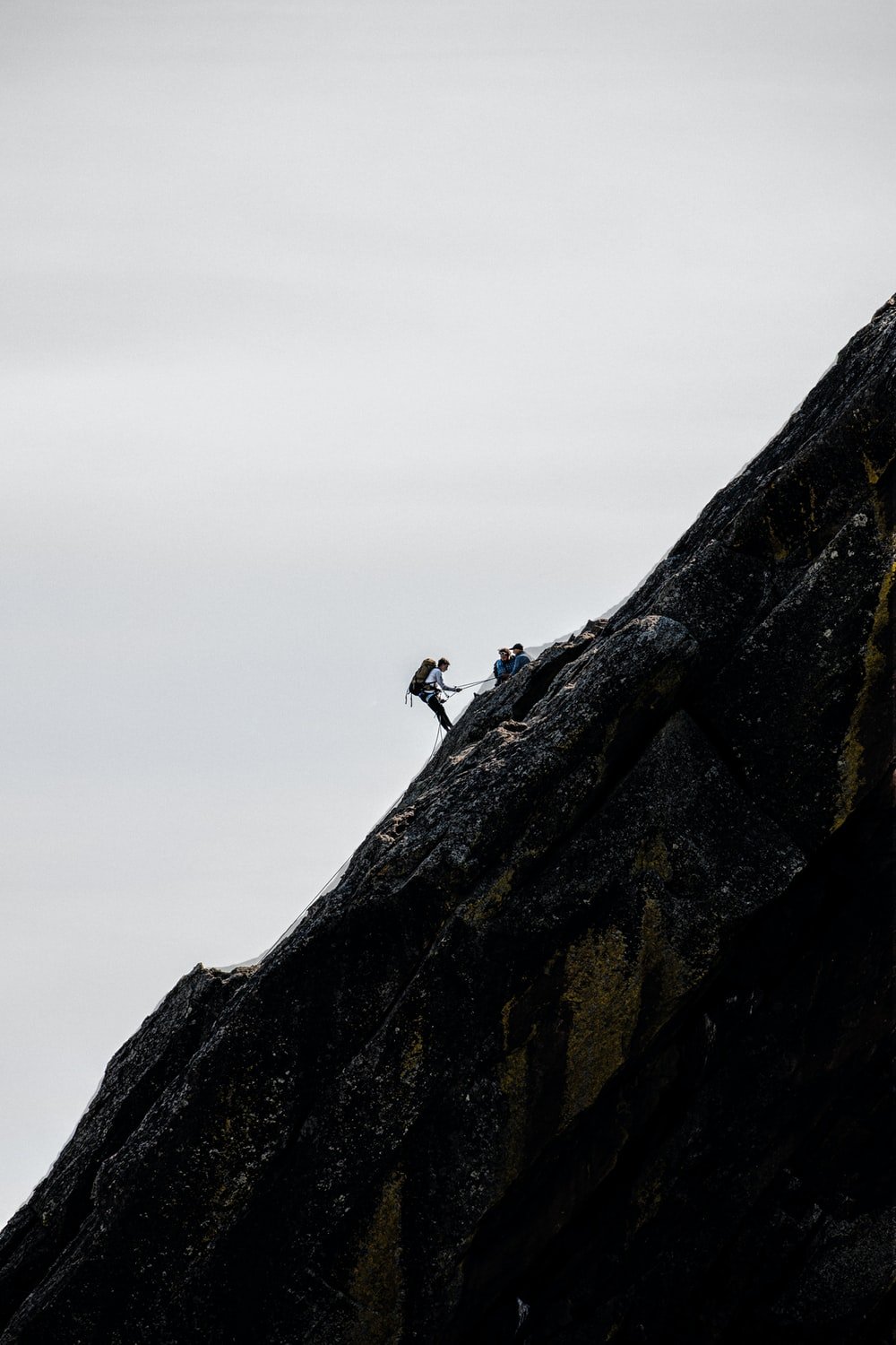 2 person climbing on rocky mountain during daytime