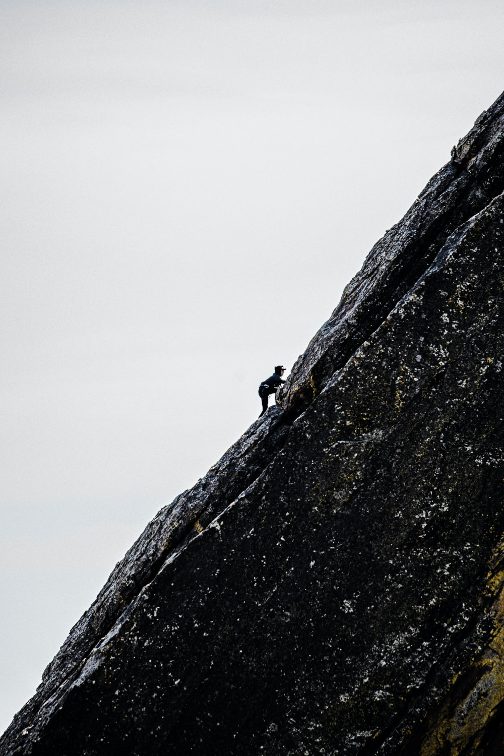 person in black jacket climbing on brown rock mountain during daytime