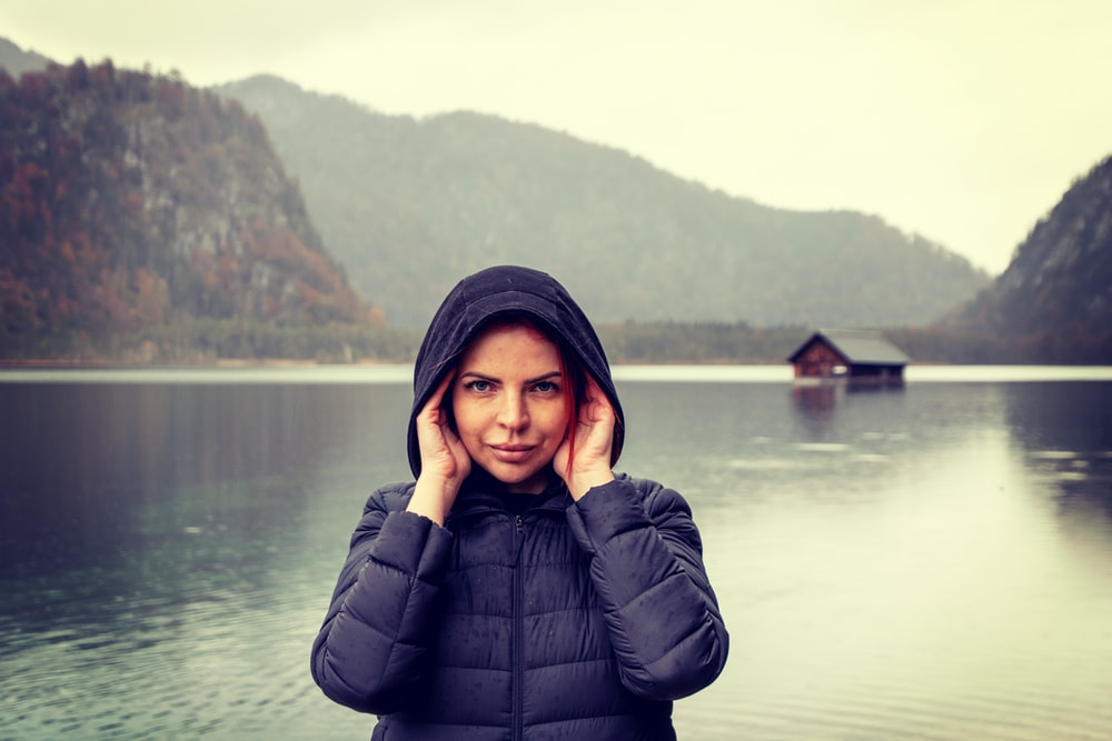 woman in black bubble jacket standing near body of water during daytime
