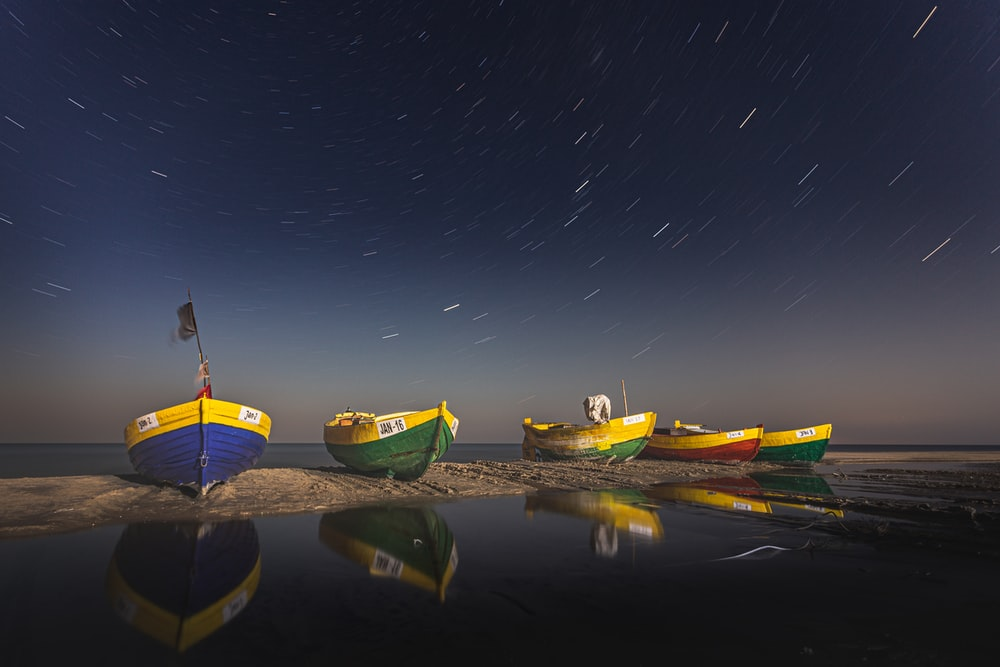 green and yellow boats on water during night time