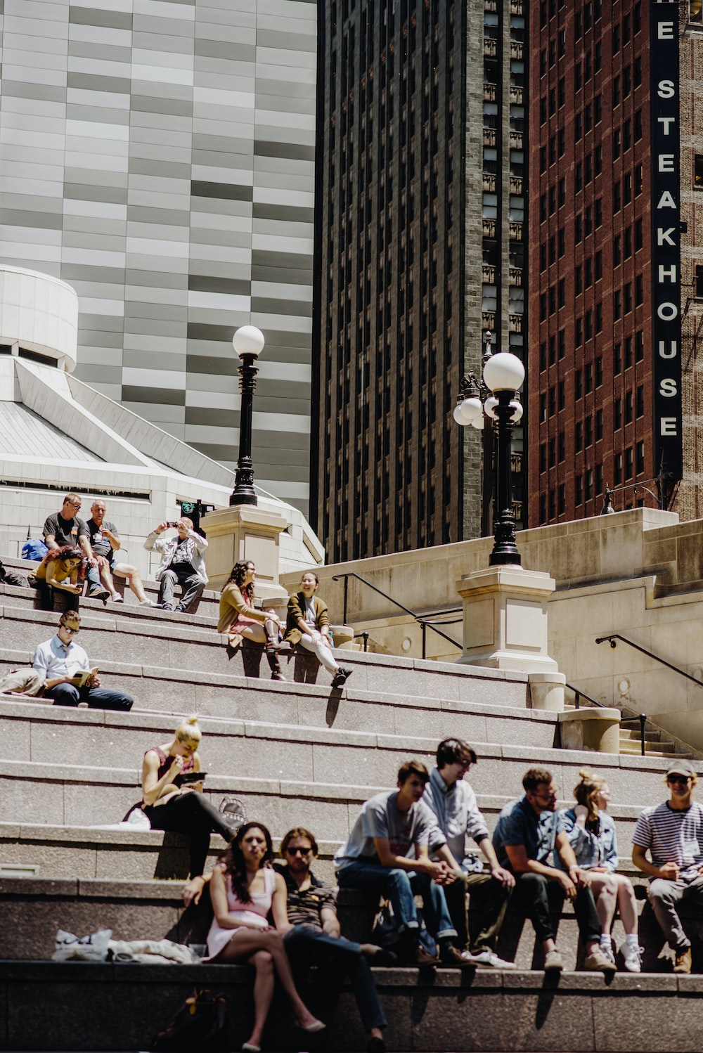 people sitting on white concrete bench during daytime