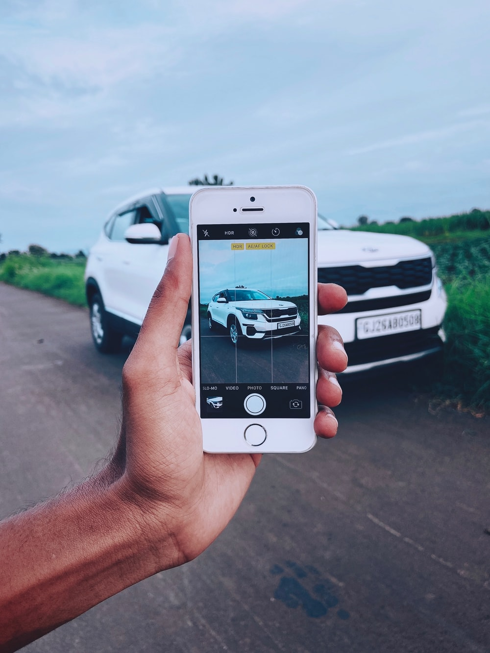 person holding silver iphone 6 taking photo of white car on road during daytime