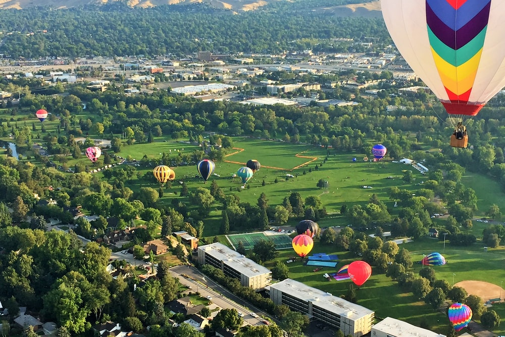 aerial view of green grass field with hot air balloons