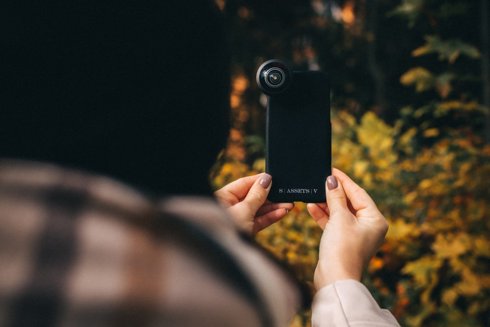 person holding black point and shoot camera